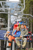 Lovely couple sitting on chairlift — Stock Photo