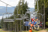 Waving young sitting on chairlift — Stock Photo