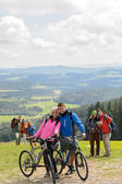 Posing cyclist couple on mountain with bikes — Stock Photo