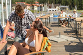 Talking young couple at beach bar — Stock Photo