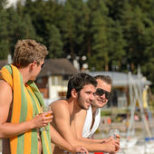 Young guys at beach drinking beer — Stock Photo