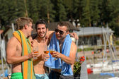 Young laughing guys in swimsuits drinking beer — Stock Photo