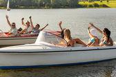 Zwaaien vrienden zitten in de motorboten zomer — Stockfoto