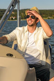 Young man navigating powerboat sunny — Stock Photo
