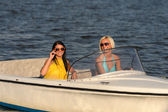 Young women in sunglasses sitting in motorboat — Stock Photo