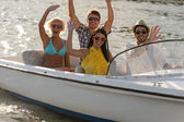 Waving young sitting in motorboat — Stock Photo
