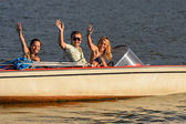 Young waving from motorboat — Stock Photo