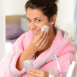 Young woman cleaning face with cotton pad — Stock Photo #23407812
