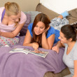 Three teenage girls reading at slumber party — Stock Photo