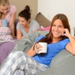 Teenager girls drinking at slumber party — Stock Photo