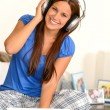 Cheerful teenager girl listening music headphones - Stock Photo
