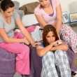 Teenager girls comfort crying friend in bedroom - Stock fotografie