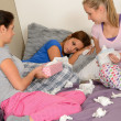 Friends consoling crying girl lying on bed - Stock Photo