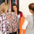Smiling teenage girl choosing the right shirt - Stock Photo