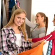 Happy teenagers choosing clothes from wardrobe — Stock Photo