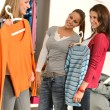 Three teenager girl choosing clothes from closet — Stock Photo