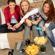 Laughing teenage girls playing with video game — Stock Photo #23408172