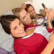 Three smiling young girl lying on bed — Stock Photo #23408174