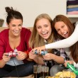 Laughing young girls playing with video games - Stock Photo