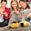 Smiling teenage girls playing with video games - Stok fotoğraf