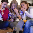 Scared girls watching horror movie on television - Stock Photo