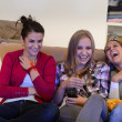 Laughing young girls watching TV together — 图库照片