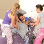 Teenager girls pillow fighting in bedroom — Stock Photo
