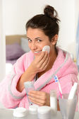 Young woman cleaning face with cotton pad — Stock Photo