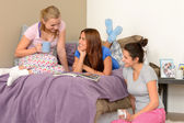 Three teenage girls talking at pajama party — Stock Photo