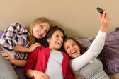Three cheerful young girls taking picture — Stock Photo