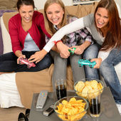 Laughing teenage girls playing with video game — Stock Photo