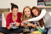Laughing young girls playing with video games — Stock Photo