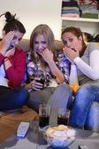 Scared girls watching horror movie on television — Foto de Stock