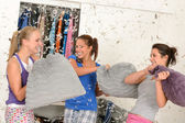 Young laughing girls during pillow fight — Stock Photo