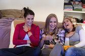 Chicas jóvenes riendo juntos viendo la tele — Foto de Stock