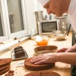 Cook in kitchen slicing chocolate cake layers — Stock Photo