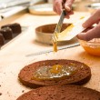 Cook making layer chocolate cake with marmalade — Stock Photo
