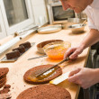 Professional cook spreading jam on cake - Foto de Stock