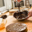 Cook kitchen dripping chocolate sauce for cake - Foto de Stock