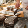 Stock Photo: Confectioner cutting slice of chocolate cake