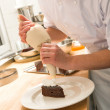Pastry chef decorating cake with frosting — Stock Photo