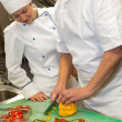 Apprentice learning cutting vegetables from chef - Stock Photo