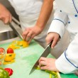 Close up of chefs cutting vegetables - Stock Photo