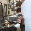 Male cook making chicken in frying pan - Foto de Stock