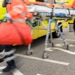 Blurry hurrying paramedics running with gurney - Stockfoto
