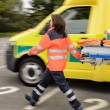 Blurry paramedics pulling gurney ambulance car — ストック写真