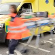 Foto Stock: Running blurry paramedics team with stretcher