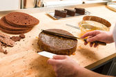 Cook spreading sauce on cake in kitchen — Stockfoto