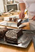 Confectioner cutting a slice of chocolate cake — Stock Photo
