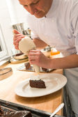Pastry chef decorating cake with frosting — ストック写真